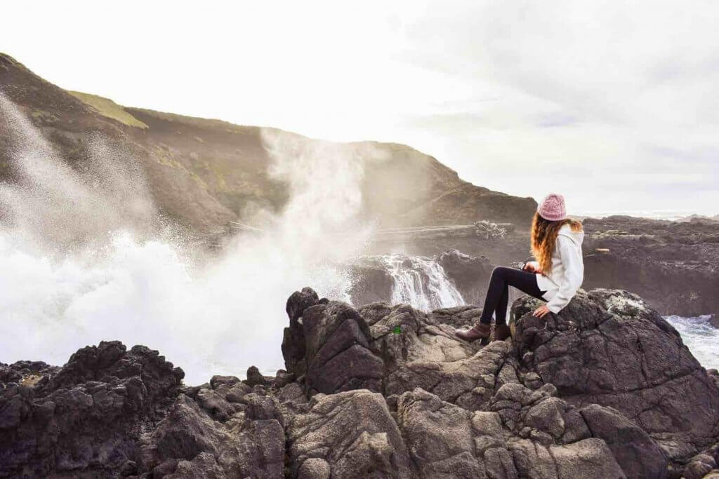Best Winter Weekend Getaways from Seattle featured by top Seattle travel blogger, Marcie in Mommyland: Image of a woman sitting near a waterfall in Yachats, Oregon in Winter