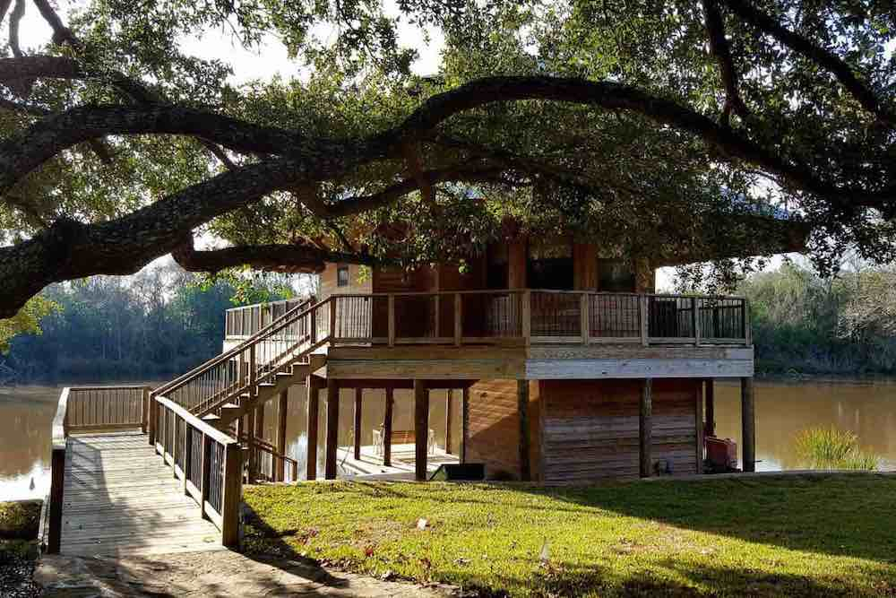 Top 7 Best Airbnbs for Christmas in the US featured by top US travel blogger, Marcie in Mommyland: Get this whole cozy cabin to yourself this Christmas. Image of a treehouse cabin by the lake.