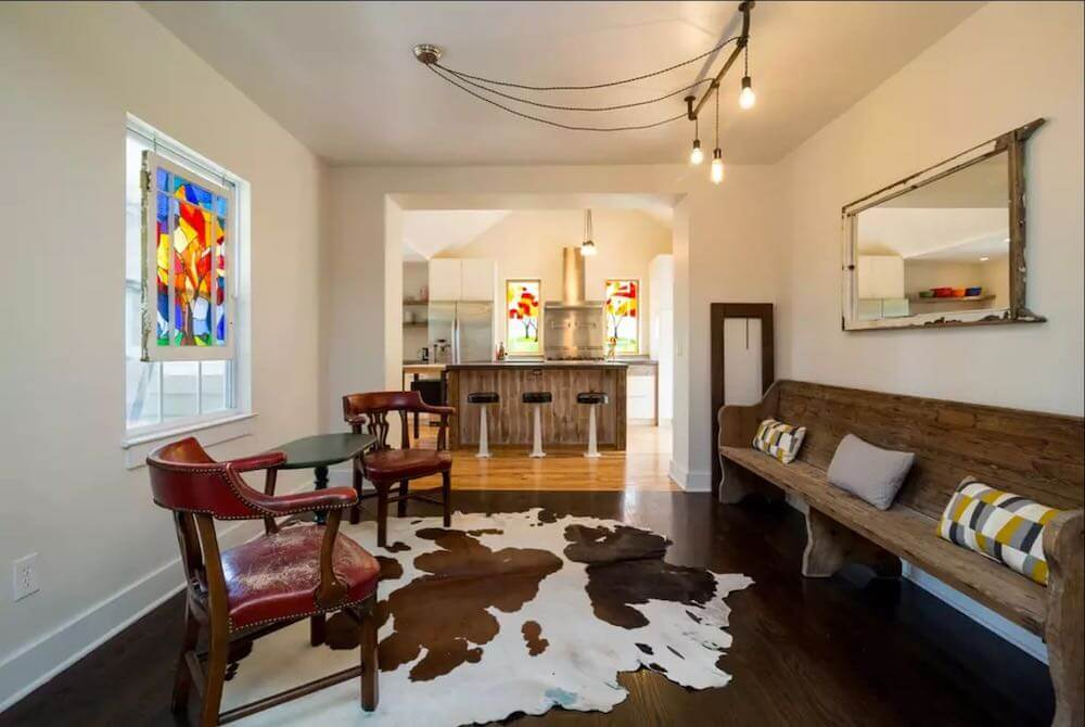 Top 7 Best Airbnbs for Christmas in the US featured by top US travel blogger, Marcie in Mommyland: Celebrate Christmas in this lovely Christmas cabin. Image of a room with a cowhide rug and antique church pew bench.
