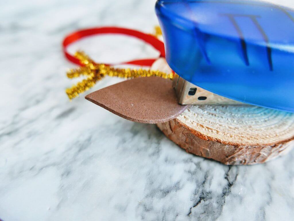 How to make a DIY reindeer ornament step 11. Image of a stapler stapling brown foam ears onto the wooden slice.