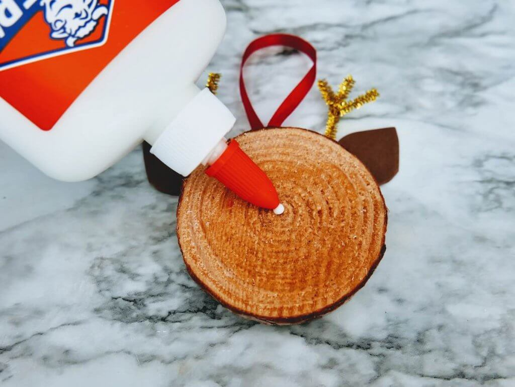 How to make a DIY reindeer ornament step 12. Image of someone putting a dot of Elmer's glue onto the wood slice.