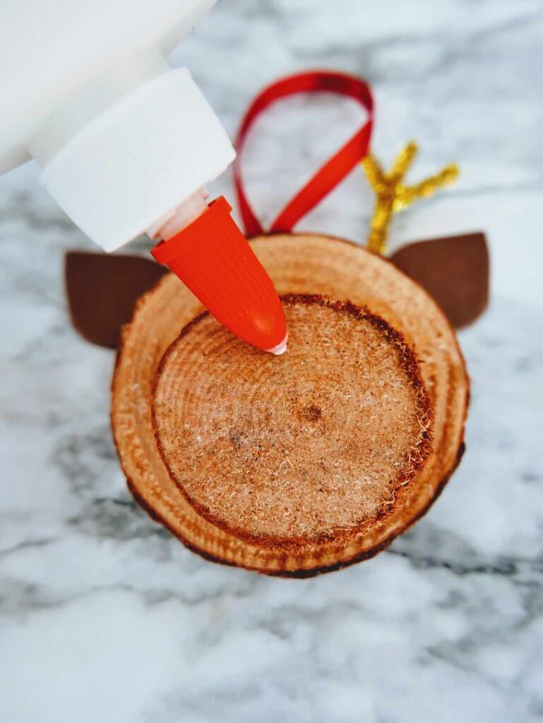 How to make a DIY reindeer ornament step 13. Image of someone gluing a red pom pom onto a small wood slice.