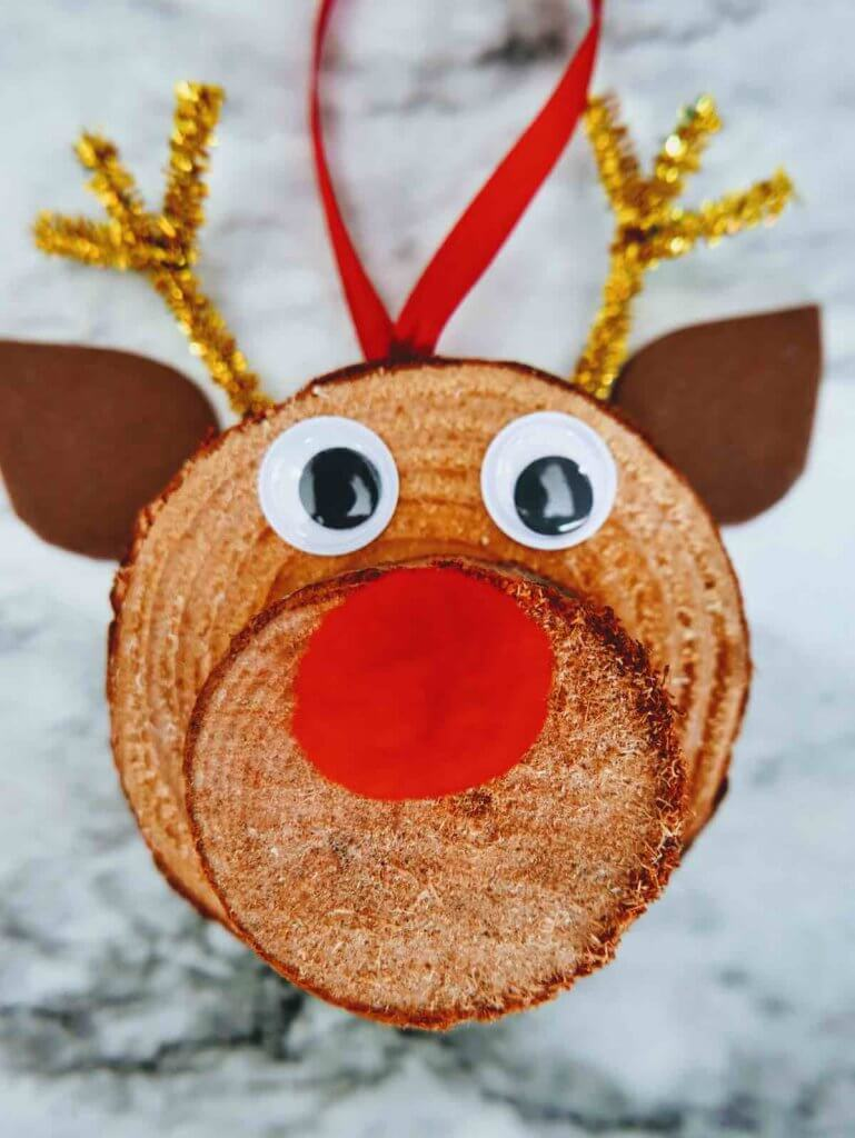 How to make a DIY reindeer ornament step 13. Image of a reindeer ornament made of wood slices with googly eyes.
