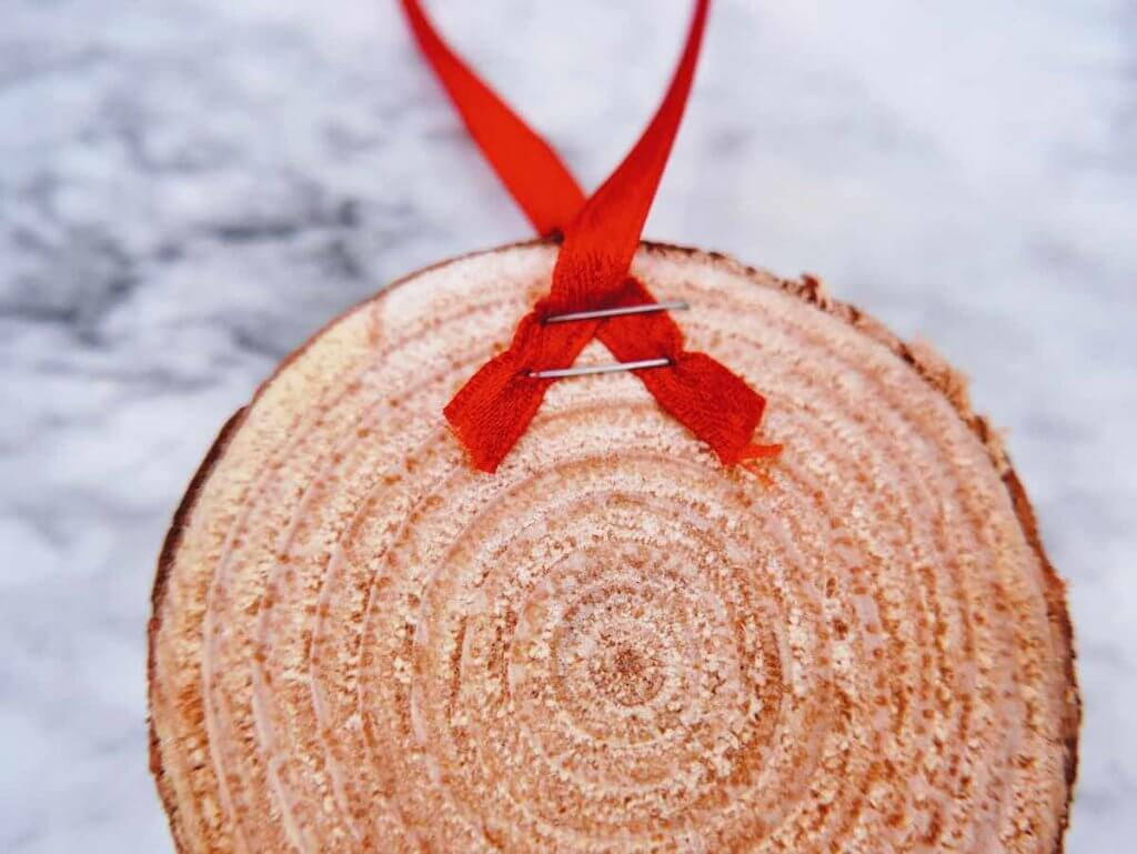 How to make a DIY reindeer ornament step 3. Image of a red ribbon stapled twice on a wood slice.