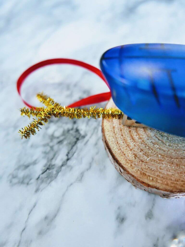 How to make a DIY reindeer ornament step 7. Image of gold pipe cleaner being stapled onto a wood slice.