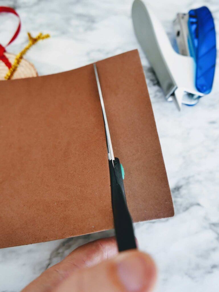 How to make a DIY reindeer ornament step 8. Image of someone cutting a strip of brown foam.
