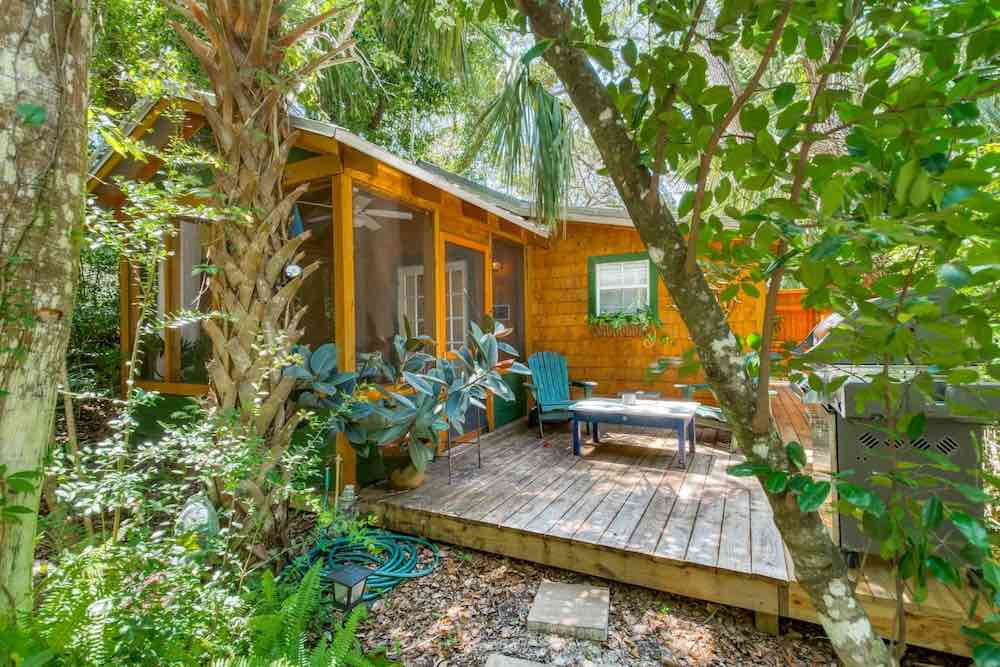 Top 7 Best Airbnbs for Christmas in the US featured by top US travel blogger, Marcie in Mommyland: Enjoy this tropical Christmas getaway in Florida. Image of a cabin surrounded by greenery.