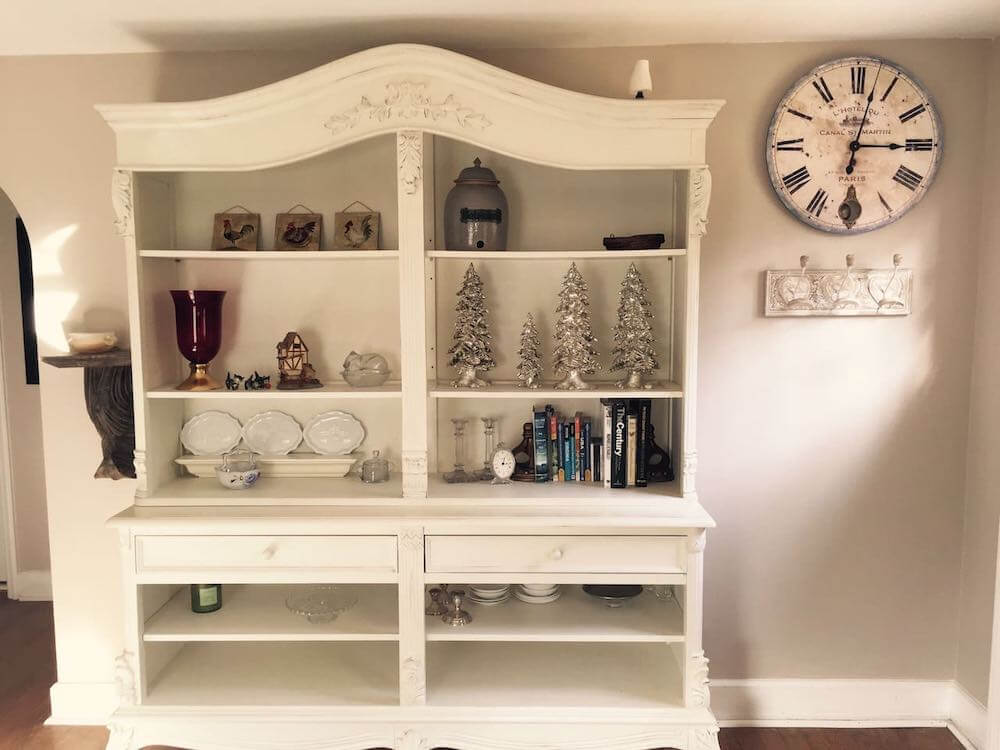 Top 7 Best Airbnbs for Christmas in the US featured by top US travel blogger, Marcie in Mommyland: Get away to this cozy Christmas cabin in Virginia. Image of a white display shelf full of Christmas decorations.