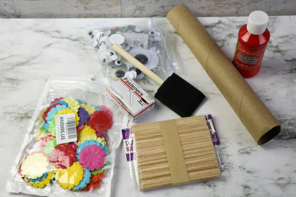 These are the materials you need to create DIY Chinese Dragon Puppets. Image of craft supplies including flowers, googly eyes, craft sticks, a paintbrush, and more.