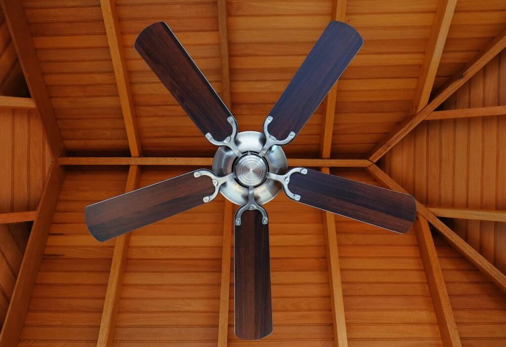 Did you know using your ceiling fan can save you money this winter? Image of a ceiling fan with a wood ceiling.