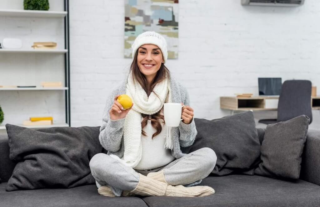 Throw on some extra layers to stay warm at home this winter. Image of a woman at home wearing a hat, scarf, sweater, and socks
