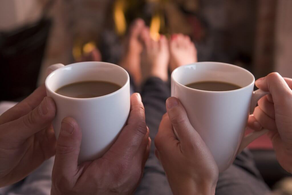 Drinking hot drinks will keep you warm this winter at home. Image of two people holding mugs of coffee in front of fireplace