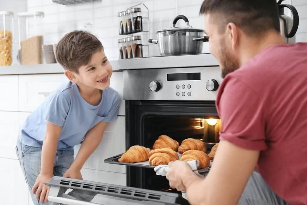 Spend time cooking with kids this New Year's Eve. Image of Little boy watching his father bake croissants in oven indoors