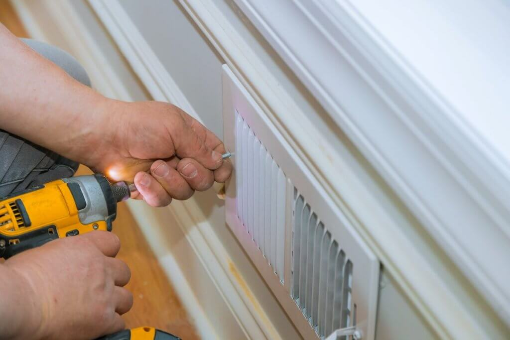 Make sure your vents aren't blocked is another cold weather hack. Image of: Maintenance repair, man is making the wall vent cover indoor central air conditioning, vents