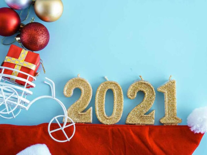 Find out easy New Years Eve Ideas for Families in this post by top Seattle lifestyle blog Marcie in Mommyland. Image of Xmas, winter, new year concept - Blue Christmas background with red gold and white tree toys, Santa hat, 2021 number candles and toy bicycle with gift in trunk. Flatly, top view, overhead. Copy space.
