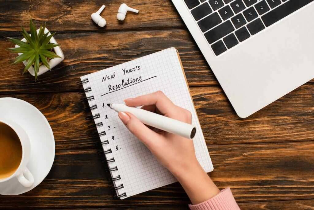 Coming up with family goals is an easy New Year's tradition with kids. Image of someone writing New Year's Resolutions in a notebook.