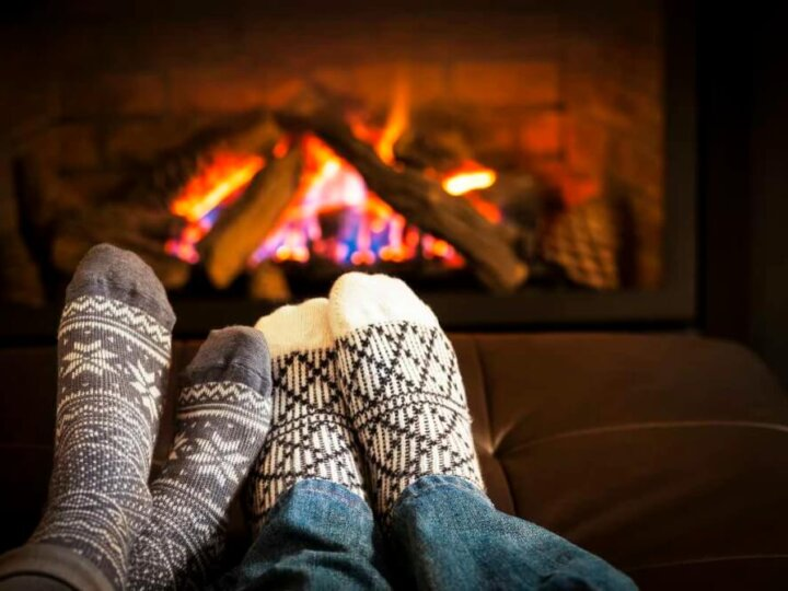 Find out how to save money this winter with these cold weather hacks.Image of: Feet in wool socks warming by cozy fire