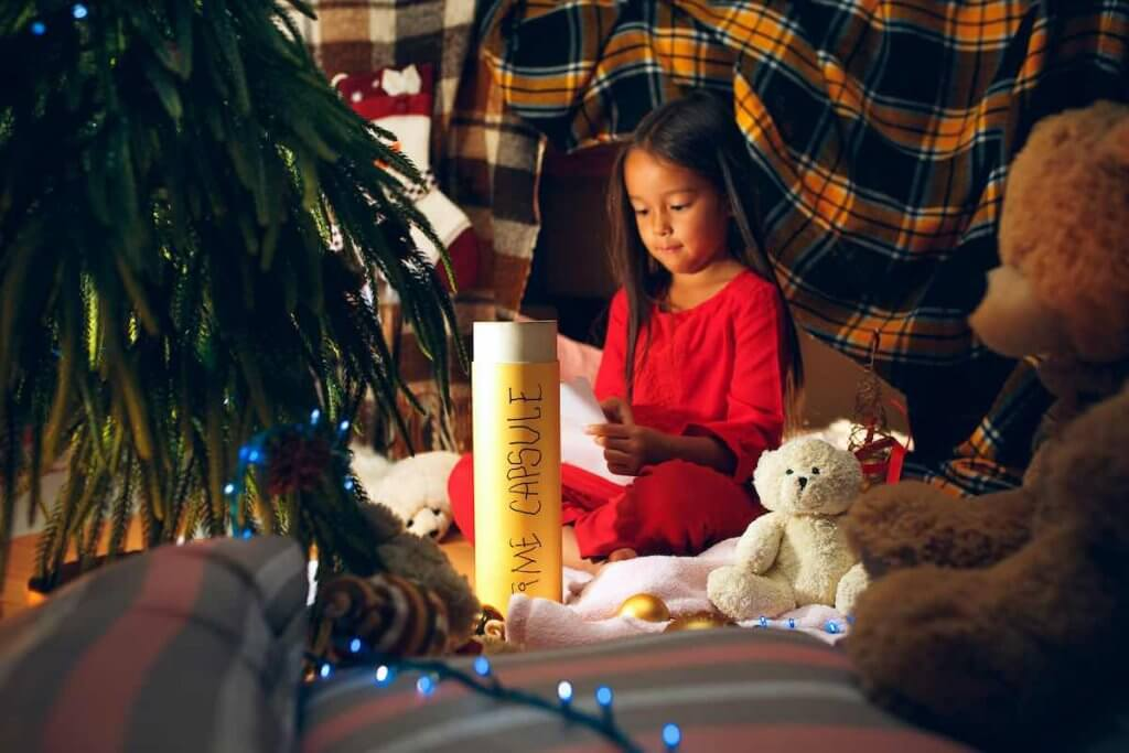 Creating a family time capsule is a fun New Year's Tradition for families. Image of Merry Christmas and Happy Holidays. Cute little child girl writes the letter to Santa Claus near Christmas tree at home indoor. The holiday, childhood, winter, celebration concept
