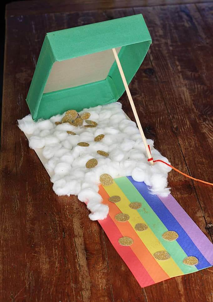 Find out how to make a leprechaun trap out of a cereal box with this DIY leprechaun trap tutorial. Image of a rainbow path with cotton balls and gold coins.