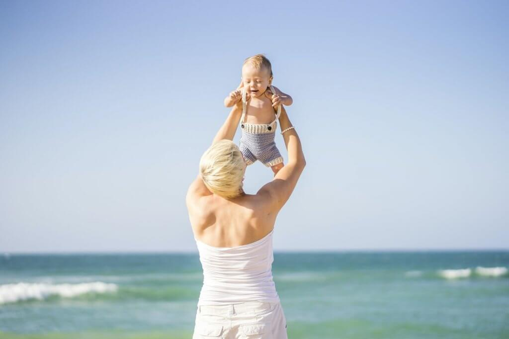Find out what to do on Maui with a baby, including the best place to stay in Maui. Image of a blonde mom holding up a baby boy near the ocean.