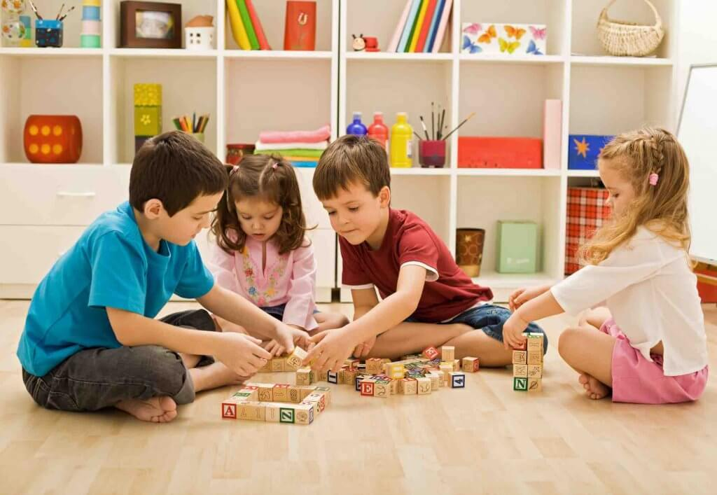 Offer to host a playdate to give other moms a break. Image of kids playing with blocks in a play room.