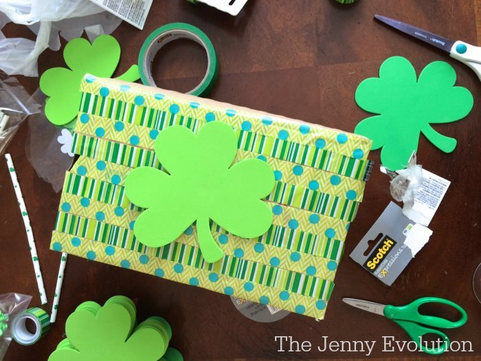 Learn how to make a leprechaun trap for kids using a shoe box. Image of a shoe box wrapped in paper with a large shamrock on top.