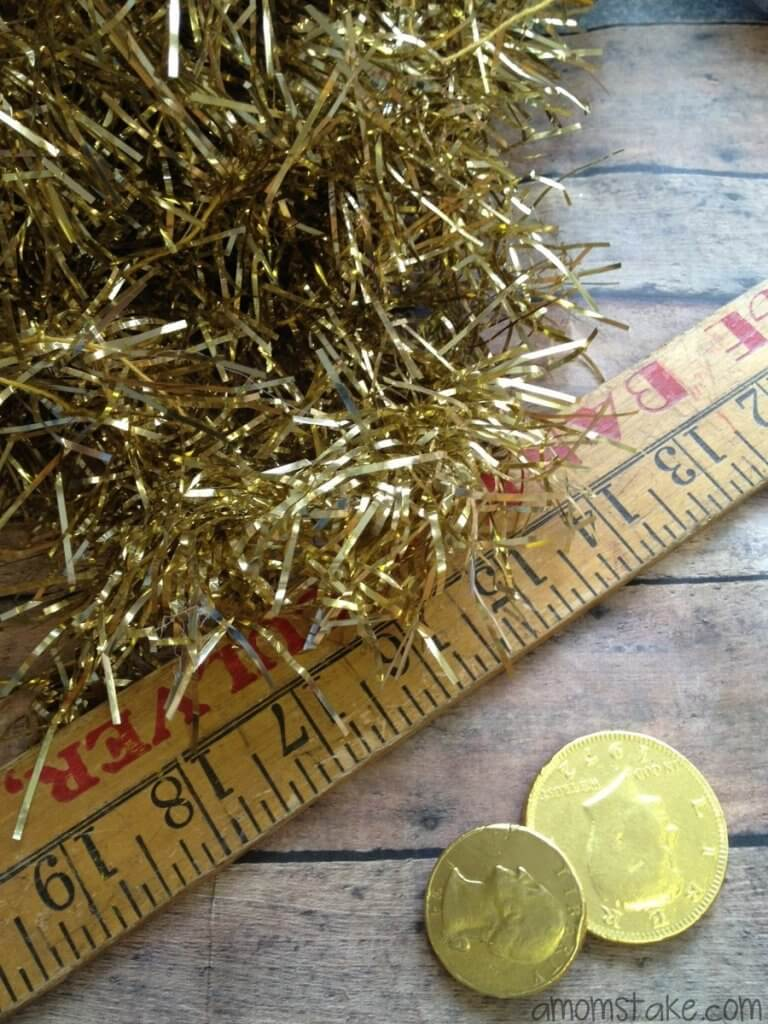 This is a super easy leprechaun trap for toddlers to make. Image of a rule, gold coins. and gold garland.