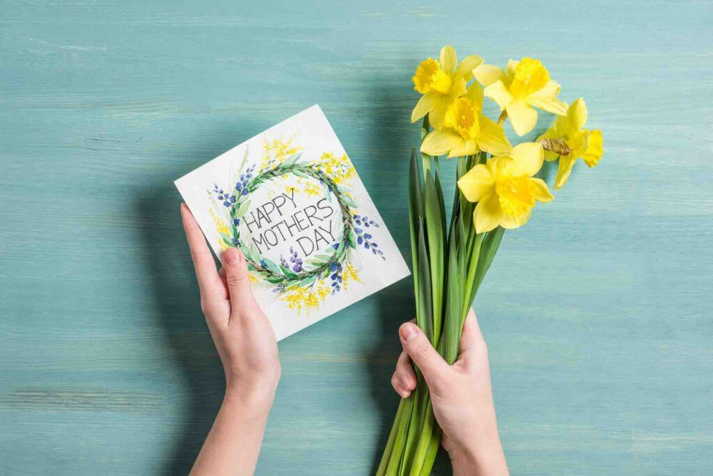 Celebrate Mother's Day with friends by telling your mom friends how much you appreciate them with a card. Image of a woman holding a Mother's Day card and daffodil flowers.