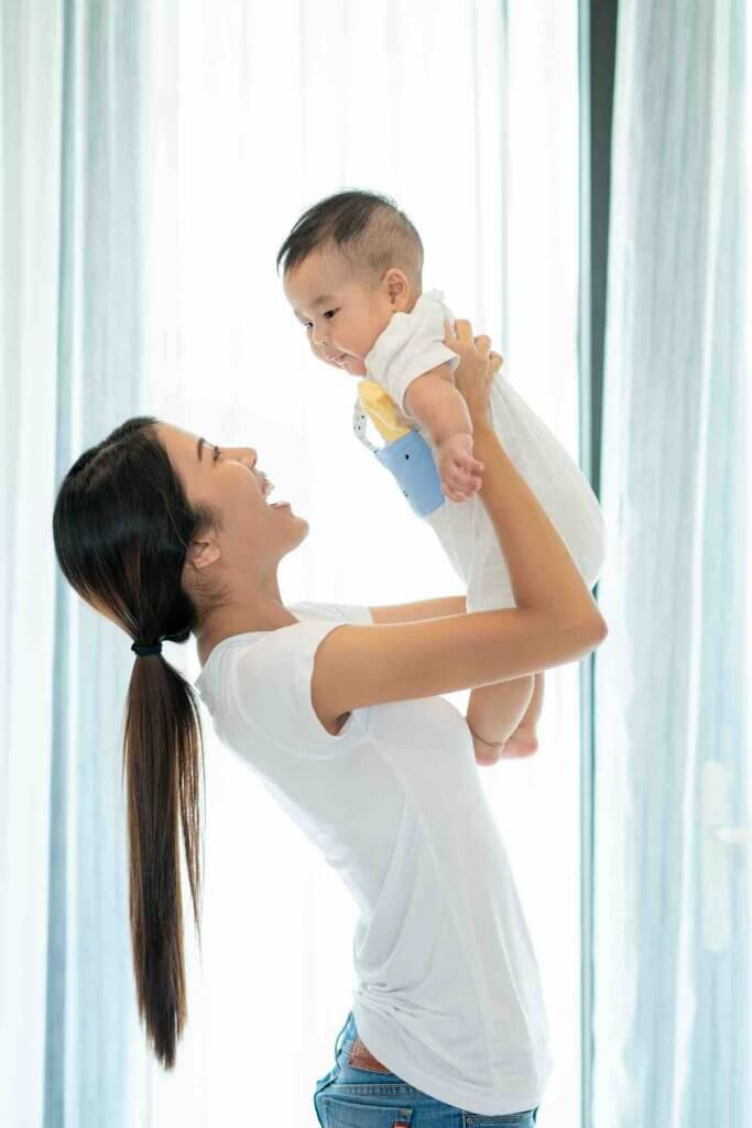 Help new moms this Mother's Day. Image of a mother playing with her baby by huge window in living room.