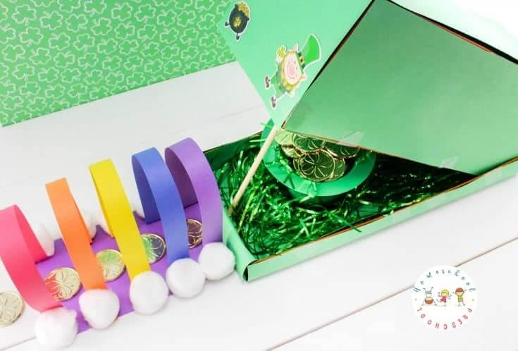 Learn how to make a leprechaun trap that is colorful and full of gold coins. Image of a green shoe box with a rainbow tunnel.