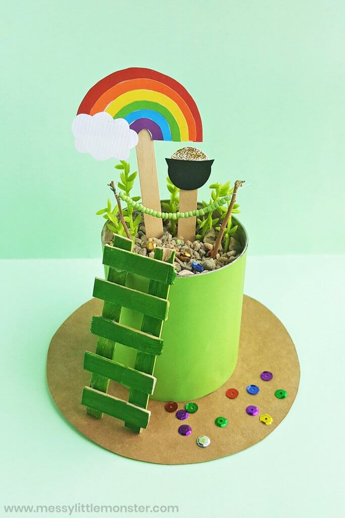Find out how to make a leprechaun trap with this easy leprechaun trap tutorial. Image of a colorful rainbow and pot of gold on popsicle sticks in a planter.