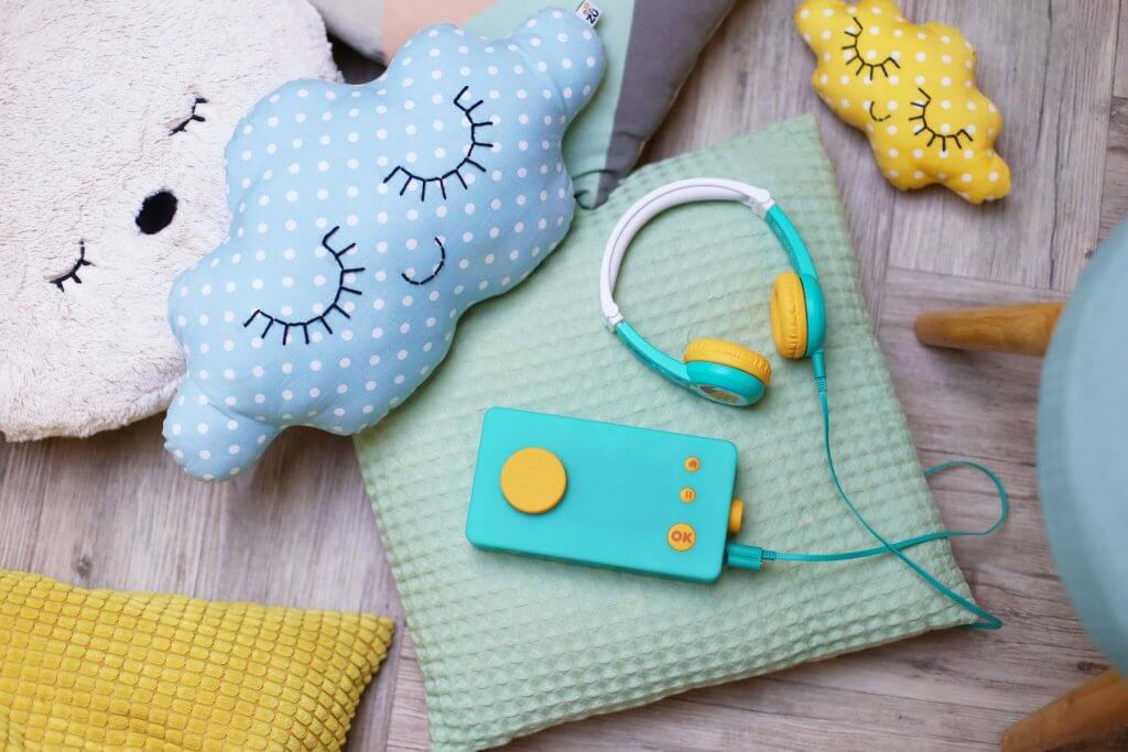 The Lunii storyteller is one of the best travel toys for toddlers. Image of a blue and yellow rectangular box with headphones on a pile of colorful pillows.