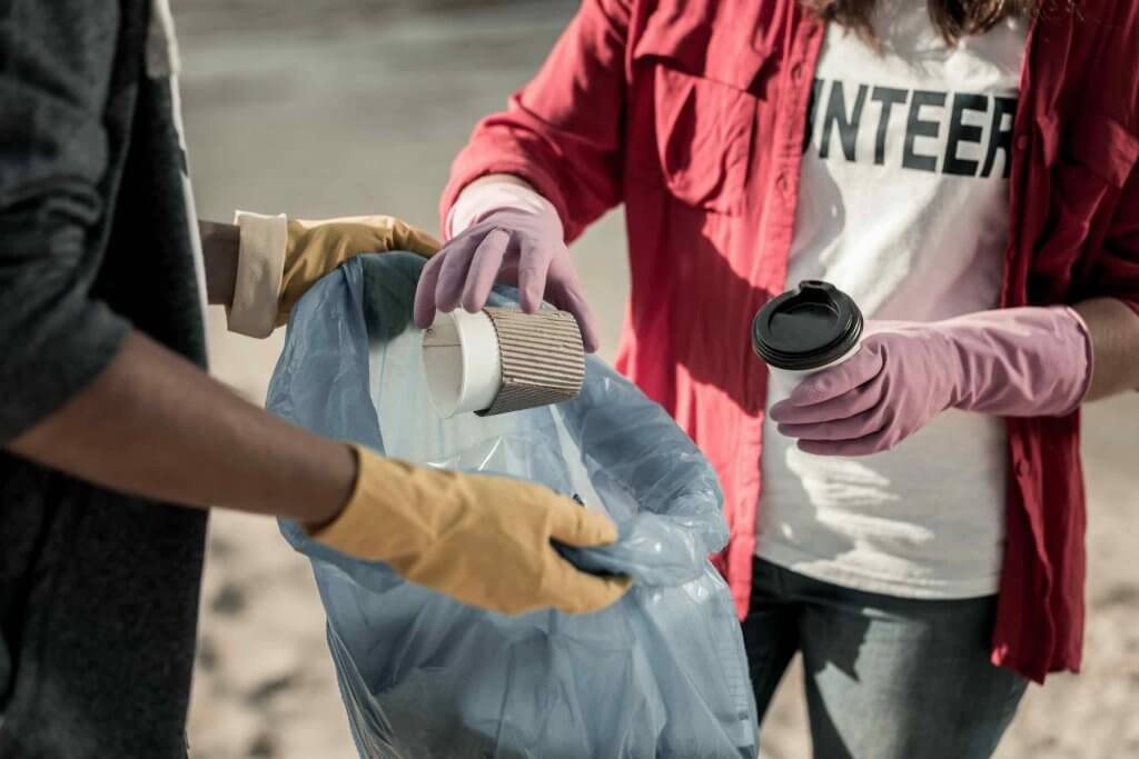 Another way to celebrate Earth Day with kids is to do a beach clean up. Image of a boy and girl wearing gloves participating in voluntary cleaning action on the beach together