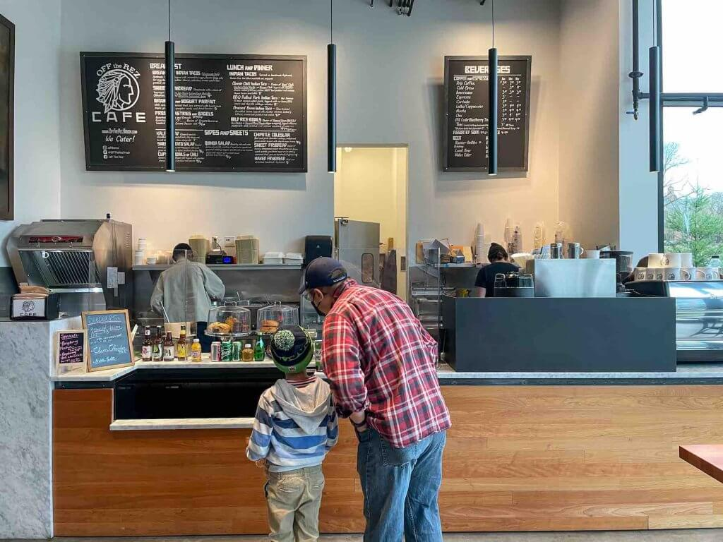 The Burke Museum cafe is run by a Native American food truck called Off the Rez. Image of a dad and son choosing what to order at the Burke Museum Cafe.