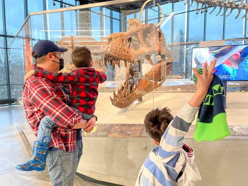 See the world's most complete T-Rex skull at the Burke. Image of a dad and two boys in front of a T-Rex skull at the Burke Museum in Seattle.