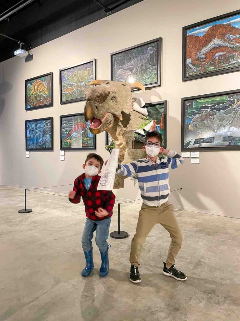 I highly recommend visiting the Burke Museum in Seattle with kids. Image of two boys dancing in front of a dinosaur display.