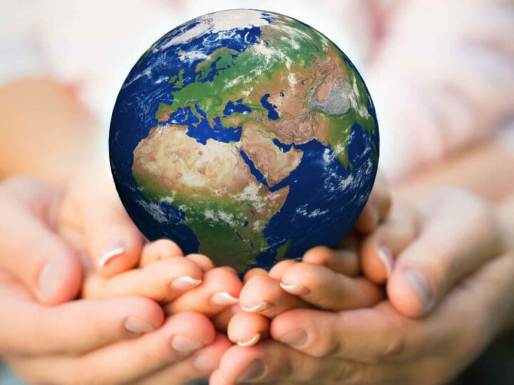 Find out 10 easy Earth Day activities for kids by top Seattle blog Marcie in Mommyland. Image of a family holding Earth in their hands.