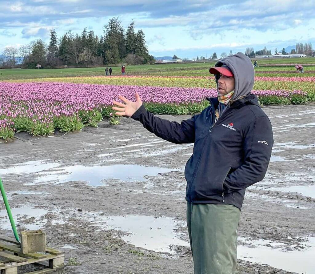 The Tulip Town Experience Pass includes a mini tulip workshop led by an owner. Image of a man in a black jacket talking to a crowd with colorful tulips in the background.
