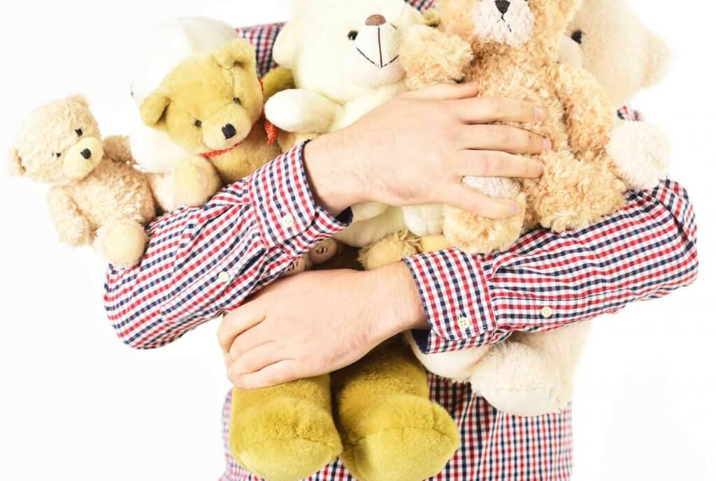 A fun Earth Day activity for kids is to do imaginative play with stuffed animals. Image of male hands with bunch of stuffed animals.