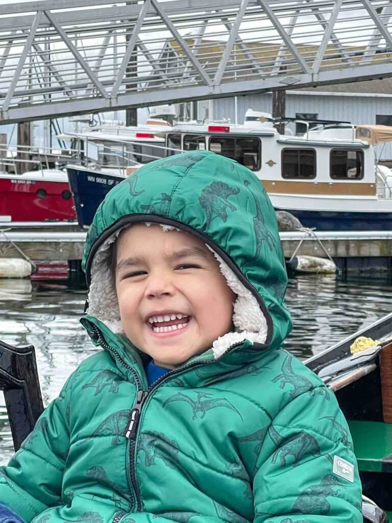 Remember to dress warmly when riding the Gig Harbor Gondola. Image of a boy wearing a green winter coat while smiling at Gig Harbor Washington.