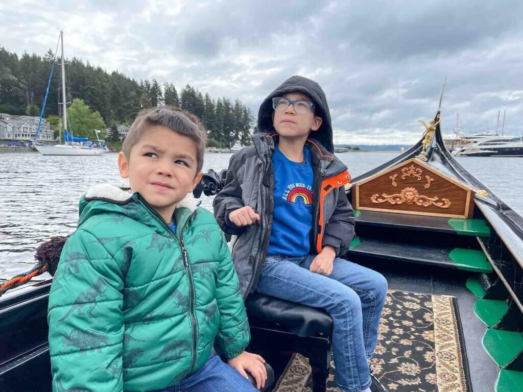 Image of two boys wearing coats riding a Venetian gondola in Gig Harbor Washington.