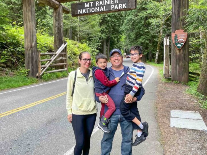 Find out the best things to do at Mt Rainier this summer by top Seattle blogger Marcie in Mommyland. Image of a family posing with the Mount Rainier National Park sign.