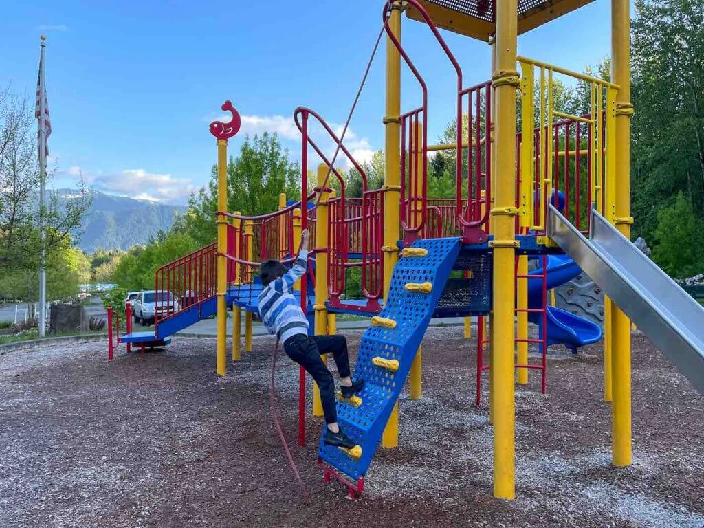 Ashford County Park is a kid friendly thing to do a Mt Rainier with kids. Image of a boy climbing on playground equipment.