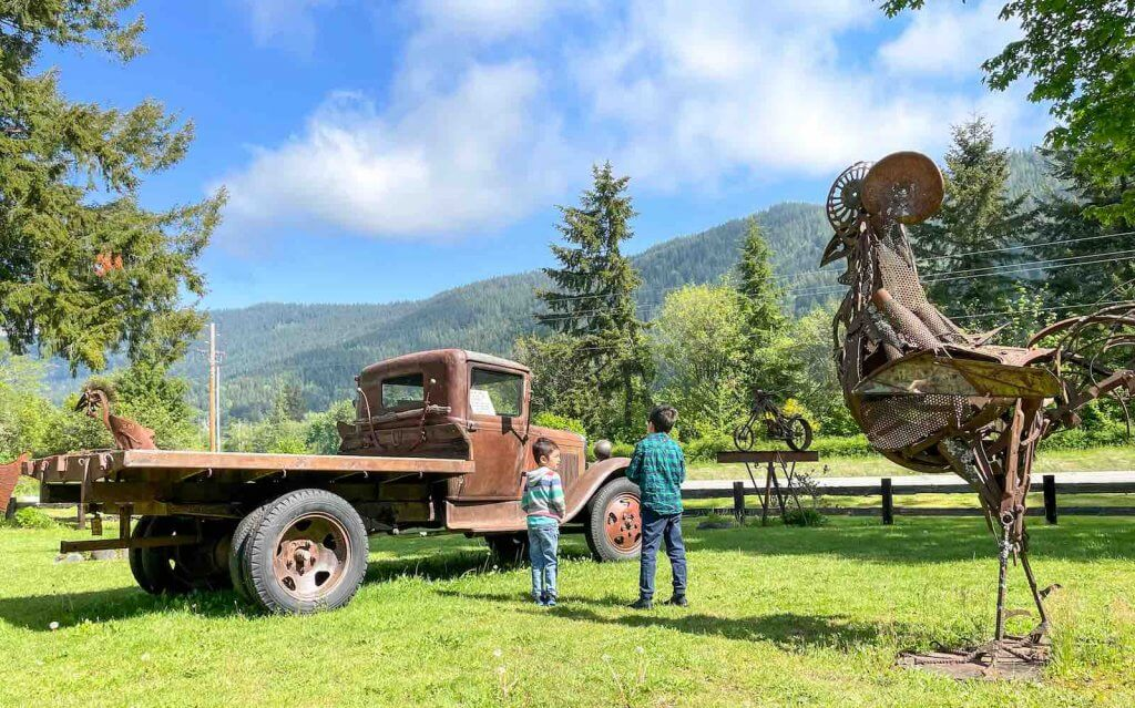 The Recycled Spirits of Iron Sculpture Park is a fun Mt Rainier attraction for families. Image of two boys standing near an old truck and giant chicken statue.