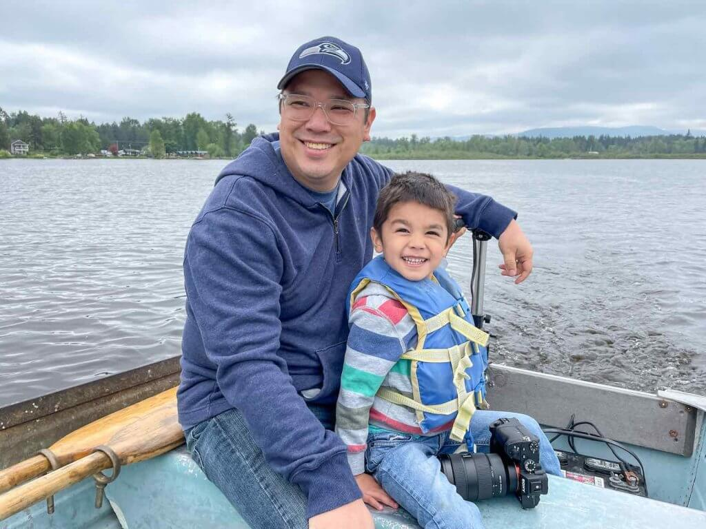 We highly recommend renting a boat from Henley's Silver Lake Resort near Mount Rainier. It's a fun thing to do at Mt Rainier with kids this summer! Image of a dad and son smiling as they steer an electric boat.