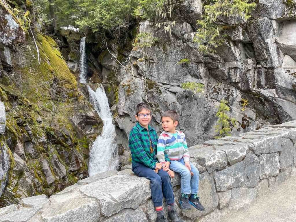 Christine Falls is one of the most popular Mount Rainier waterfalls for families because it doesn't require a hike. Image of two boys sitting in front of Christine Falls at Mount Rainier National Park.