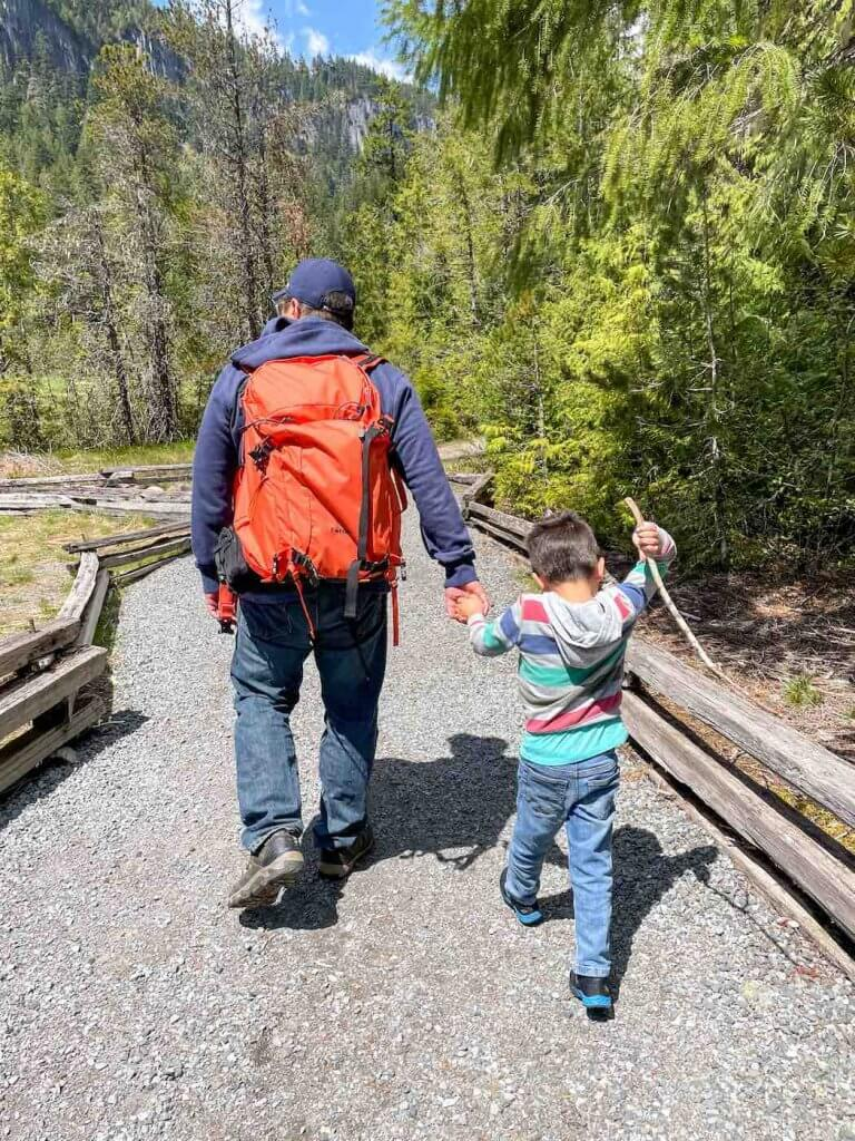 The Trail of Shadows is one of the best Mt Rainier hikes for kids. Image of a dad and son walking on a gravel path at Mount Rainier National Park.