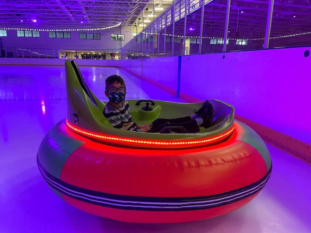 You can drive ice bumper cars in Spanaway, WA. Image of a boy sitting in an ice bumper car inside an ice skating rink.