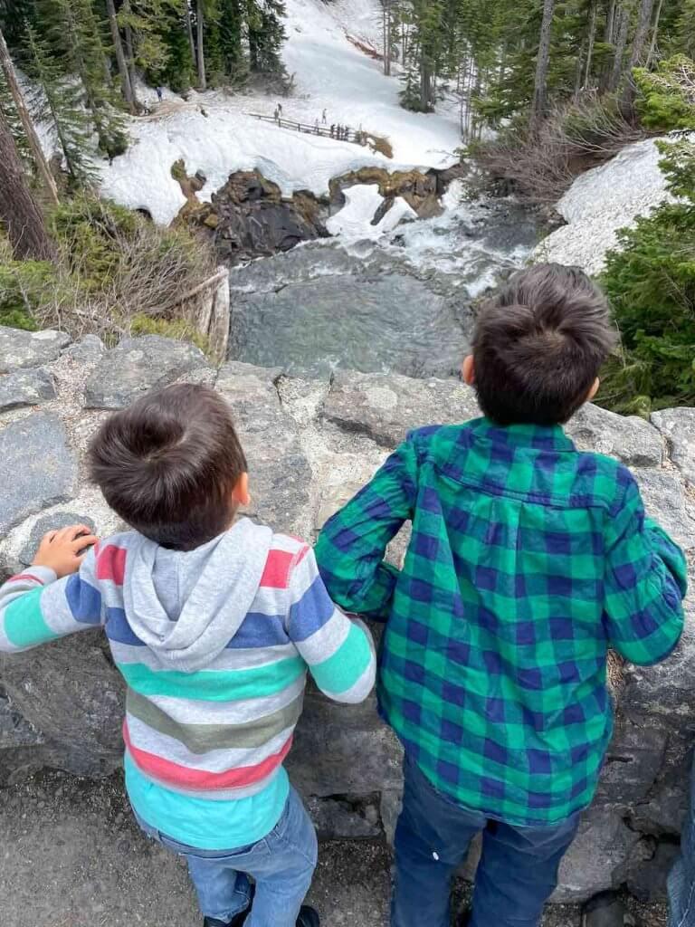 From the bridge, you can look down at Narada Falls at Mount Rainier National Park. Image of two boys looking at Mt Rainier waterfalls.