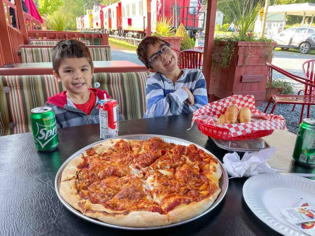 Pizza Express is a kid friendly place to eat near Mount Rainier National Park. Image of two boys smiling in front of a tray of pizza.